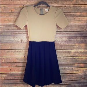 Beige and black dress with pockets.